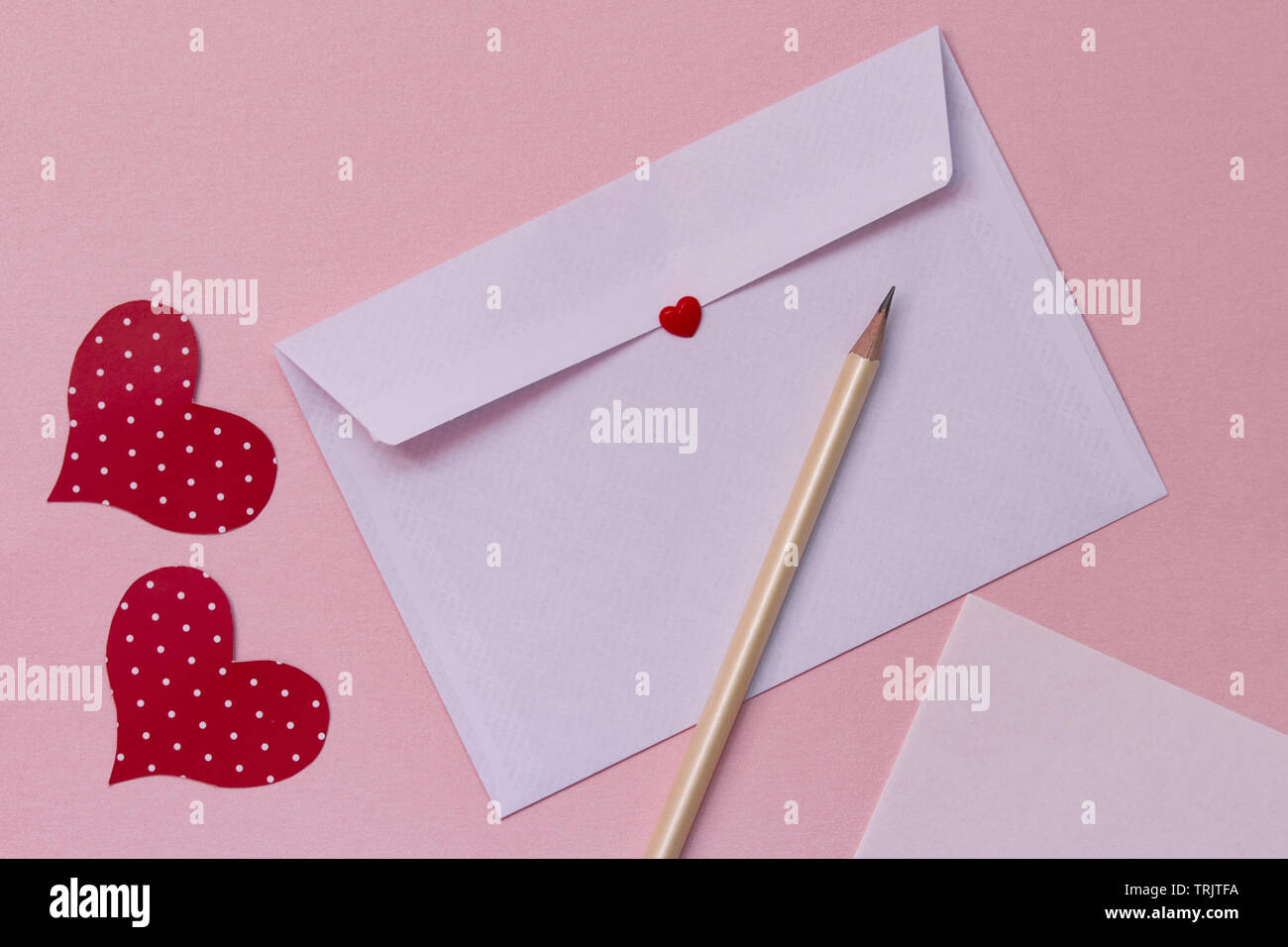 Love letter on a pink background. white paper envelope mock up. love correspondence concept - Stock Image