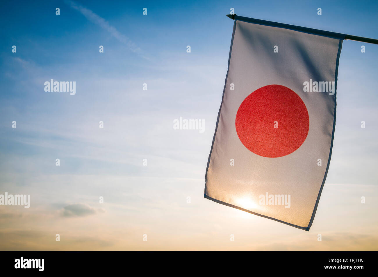 Japanese flag hanging outdoors in the still golden light of the rising sun in Tokyo, Japan - Stock Image