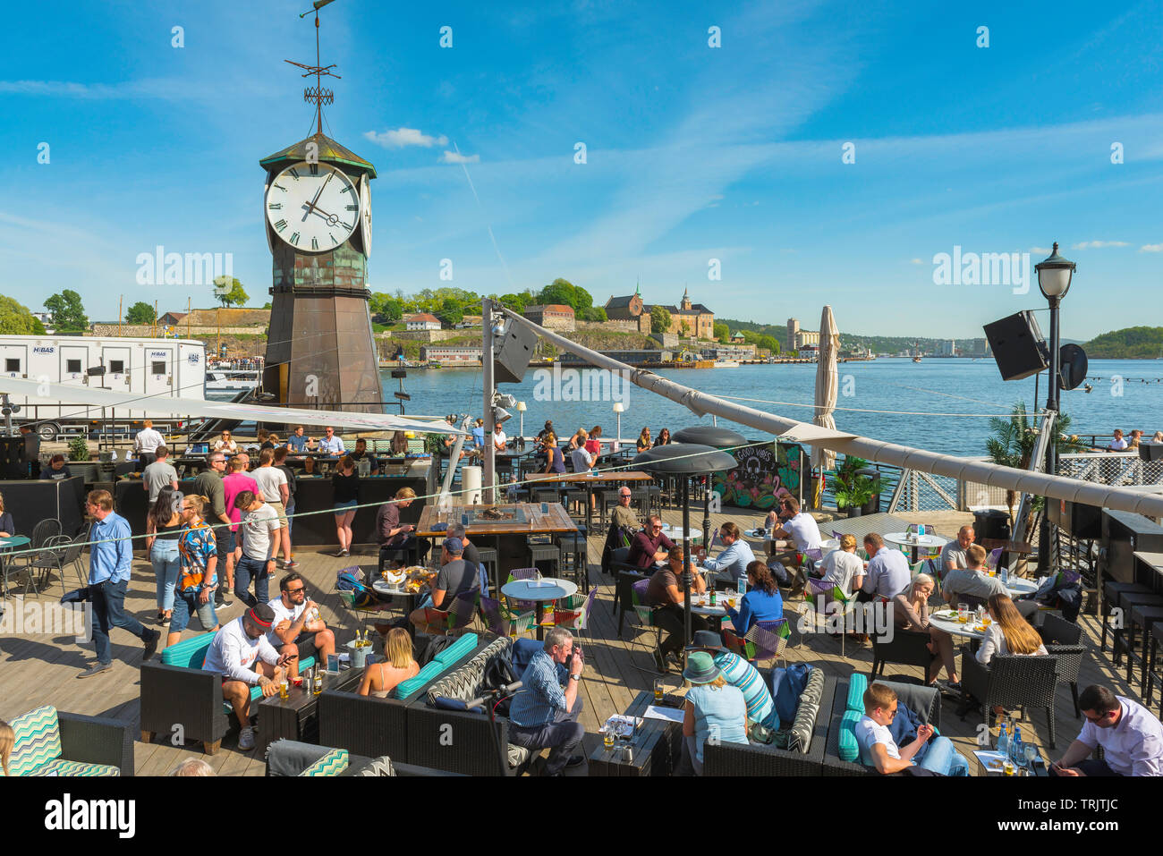 Oslo Aker Brygge, view of people relaxing on a summer afternoon on a terrace bar along the Stranden in the Aker Brygge harbour area of Oslo. Stock Photo