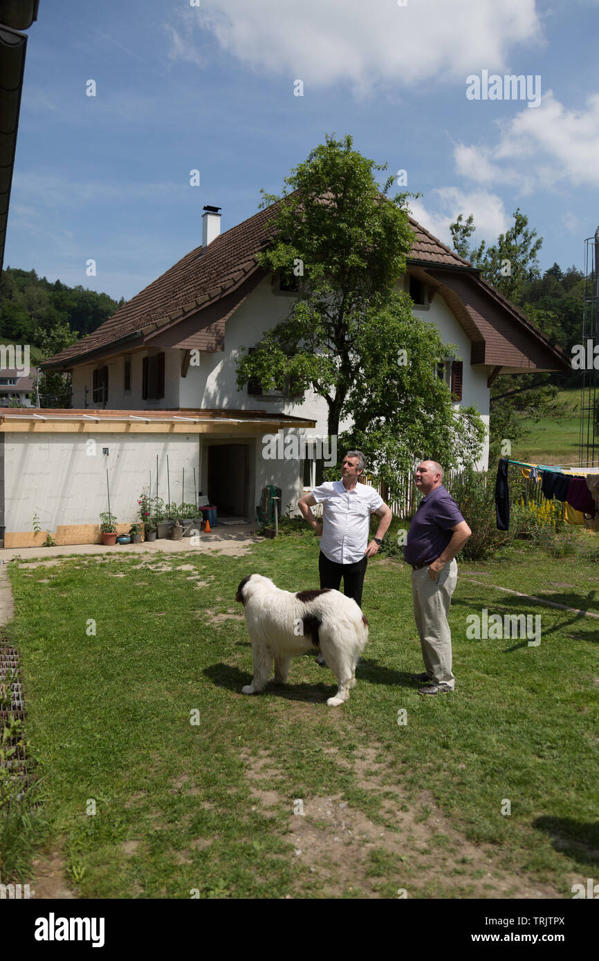 Two men talking behind an old 19th century Swiss farmhouse in Aargau, Switzerland. - Stock Image