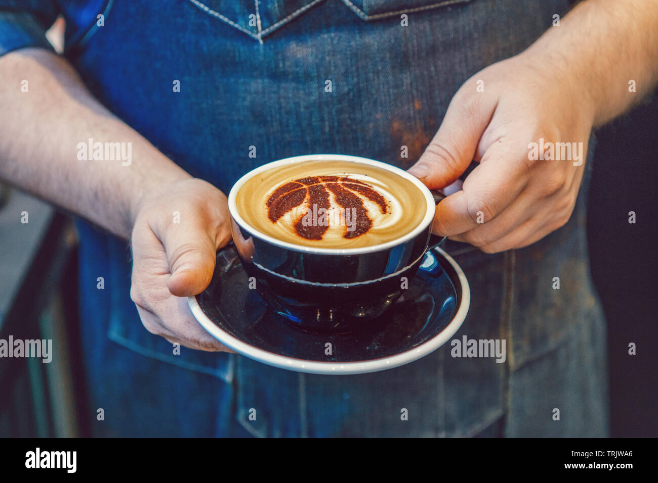 Toronto, Ontario, Canada - June 6, 2019: Closeup of barista hands holding black cup of coffee cappuccino with Toronto Raptors basketball team logo - Stock Image