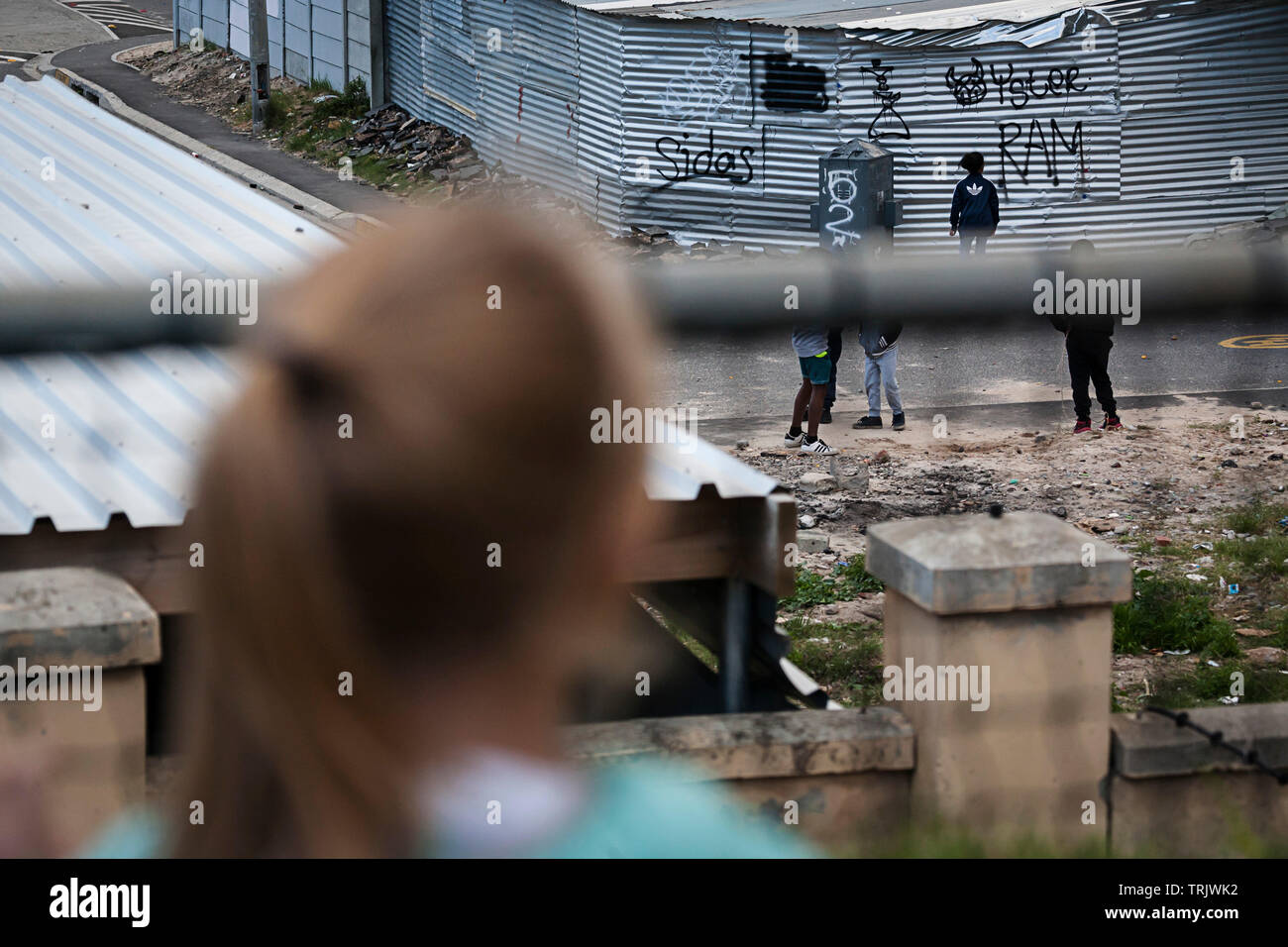 Young girl looking at children playing in the street in a township in Africa from across a fence. - Stock Image