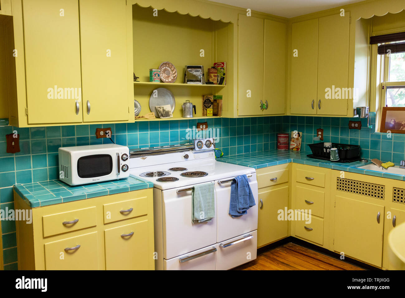 Retro 1940s Style Kitchen With Yellow Cabinets And Blue Tile