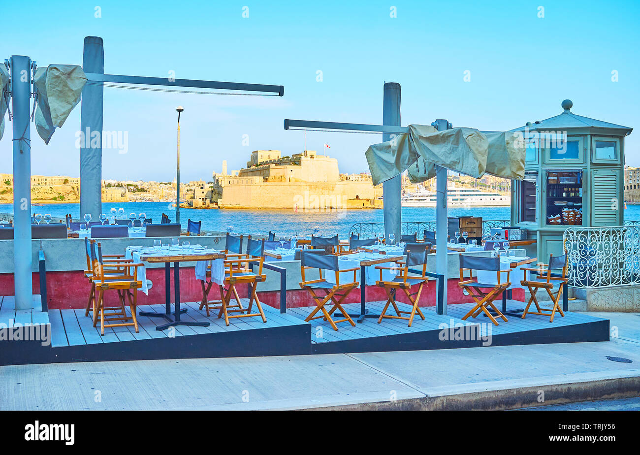 The small outdoor cafe in Briiera Wharf overlooks the Great Harbour of Valletta and Fort Sta Angelo of Birgu, Malta - Stock Image