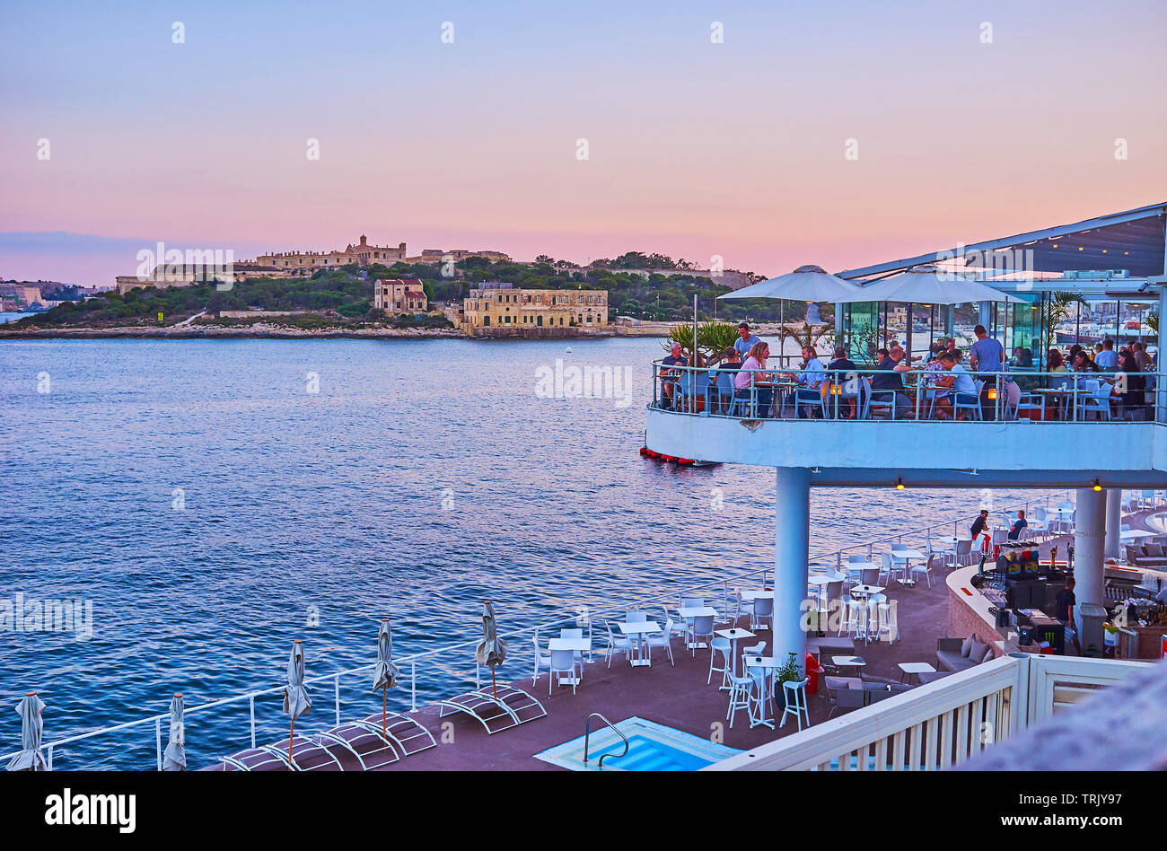 SLIEMA, MALTA - JUNE 19, 2018: The crowded open air terrace of the coastal restaurant on Tigne Point peninsula with a view on Valletta Northern Harbor - Stock Image