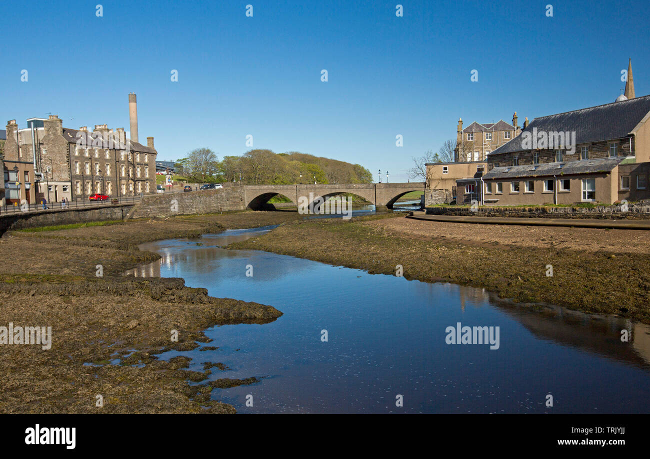 Town of Wick in Caithness Scotland with buildings beside river and bridge, and blue sky reflected in calm water - Stock Image