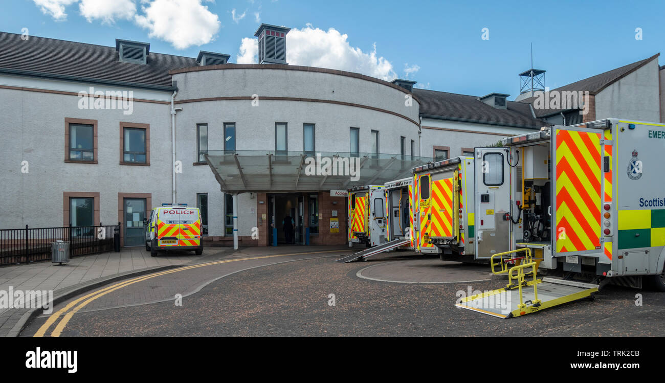 Four emergency ambulances and a police car parked outside the entrance to the Accident and Emergency Unit of the University Hospital, Wishaw, North La - Stock Image