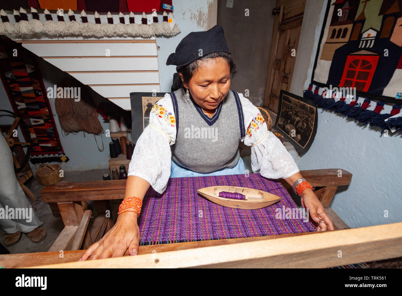 A woman weaving with spindle and loom in Peguche, a village of weavers near Otavalo, Ecuador, South America. - Stock Image