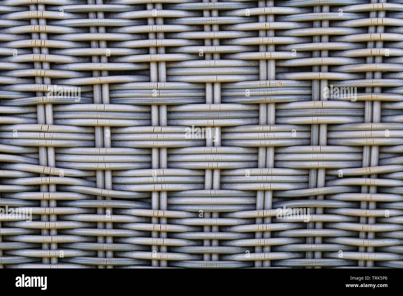 Rattan chair in a closeup. Beautiful symmetric texture of the surface is great as a background photo. Lovely detailed macro image of grey surface. - Stock Image
