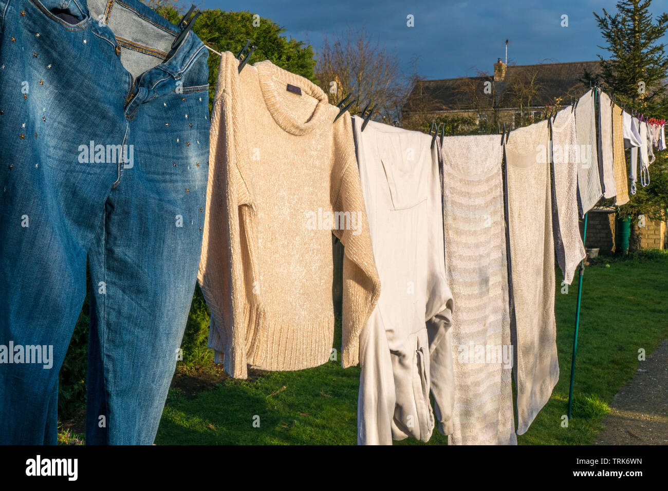 Side view of domestic laundry of wet clothes and towels, pegged and hanging out to dry on a washing line in the warm afternoon sunshine. England, UK. - Stock Image