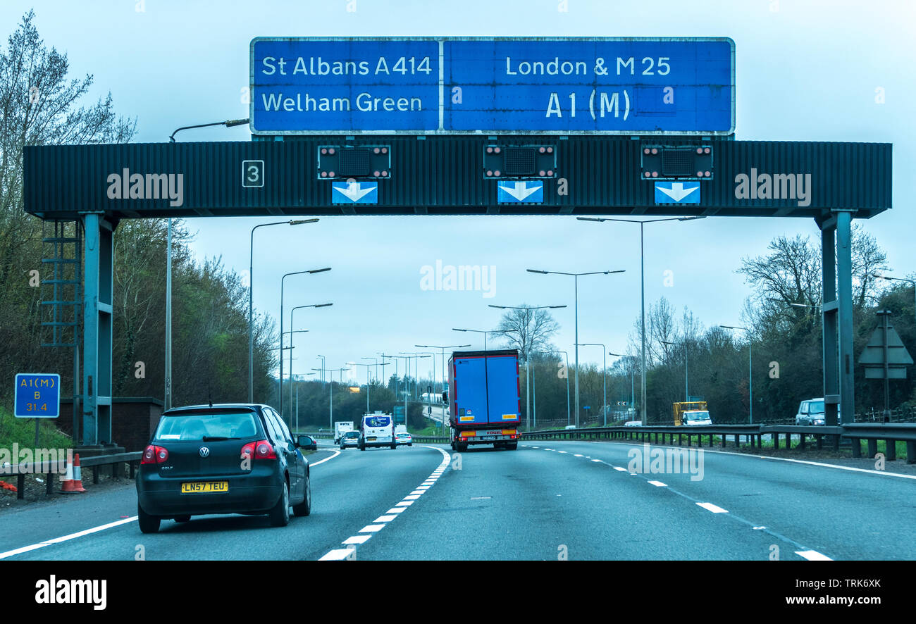 Traffic on the A1 motorway in North London, leading to the M25. The inside lane is forming the turn off, as shown on the overhead gantry. England, UK. - Stock Image
