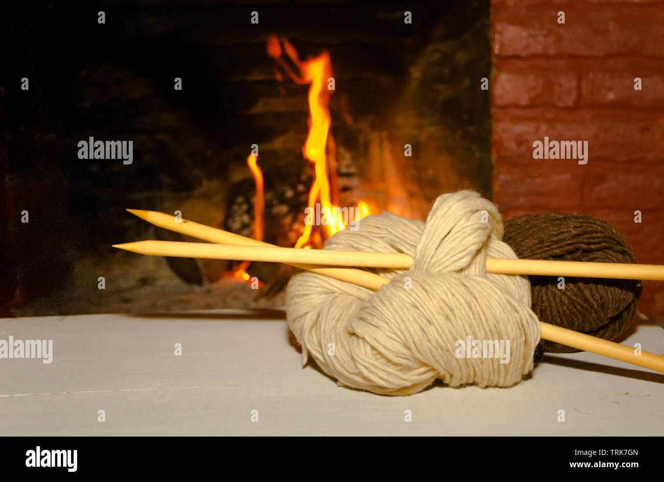 winter concept knitting wool and tricot needles with fire from home on wood background - Stock Image