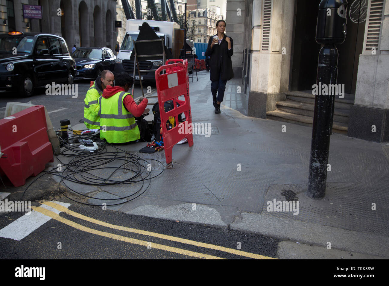 Telecoms engineers working on cable cabling in city of London Street - Stock Image
