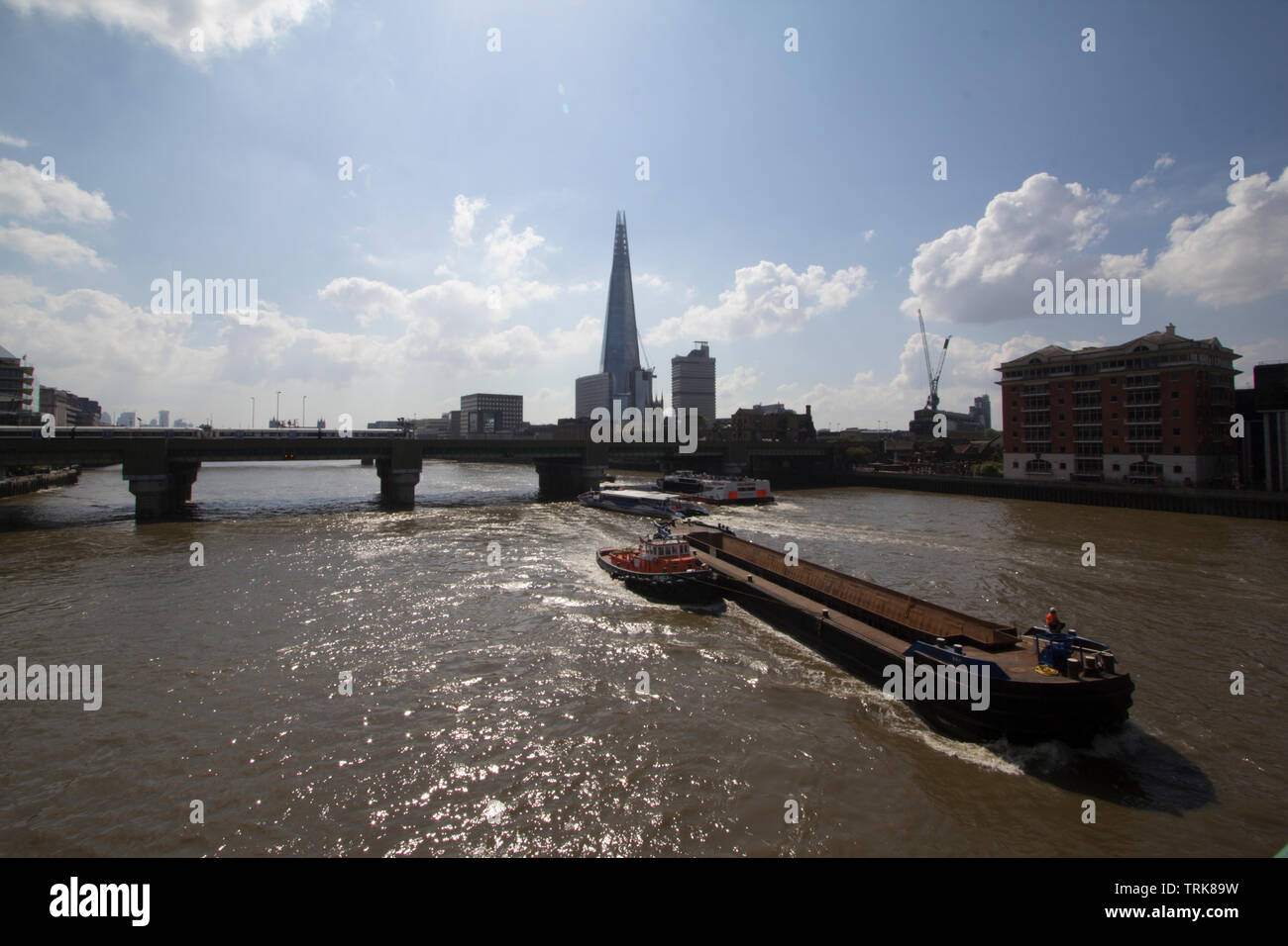 Barge belonging to Cory Environmental, the largest barge operator on the Thames, passes between Cannon Street railway bridge and Southwark Bridge on the River Thames, with tug boat and Shard in background - Stock Image