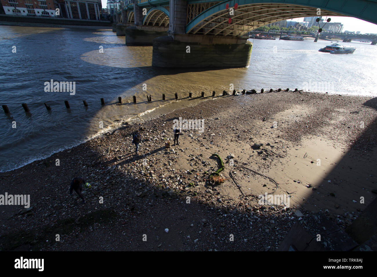 Mudlarkers searching the bank of the River Thames under Southwark Bridge - Stock Image