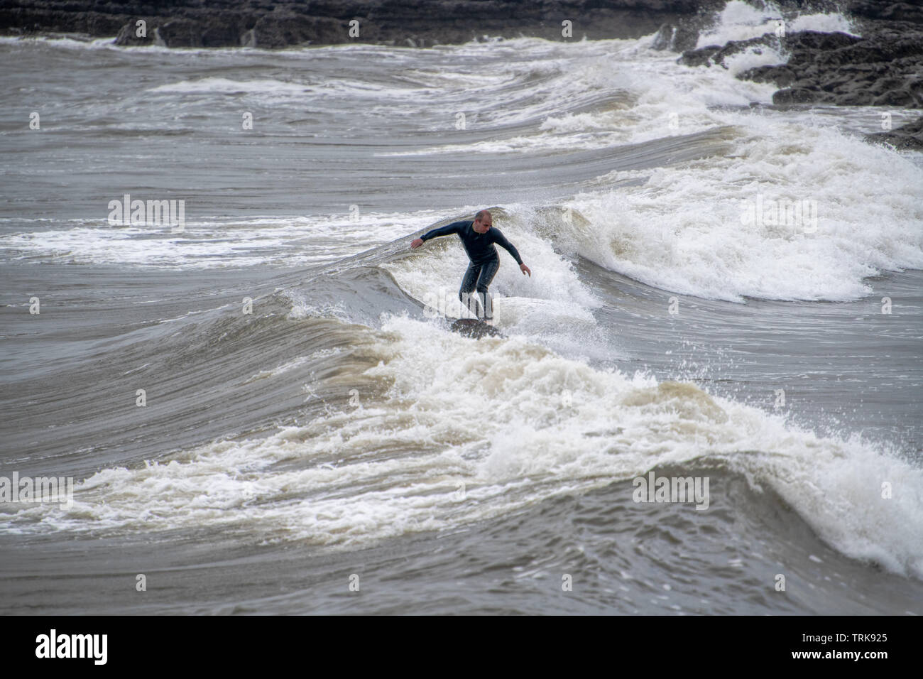 A middle-aged surfer in wet suits hols his balance in tricky water. Rest Bay Porthcawl, UK. - Stock Image