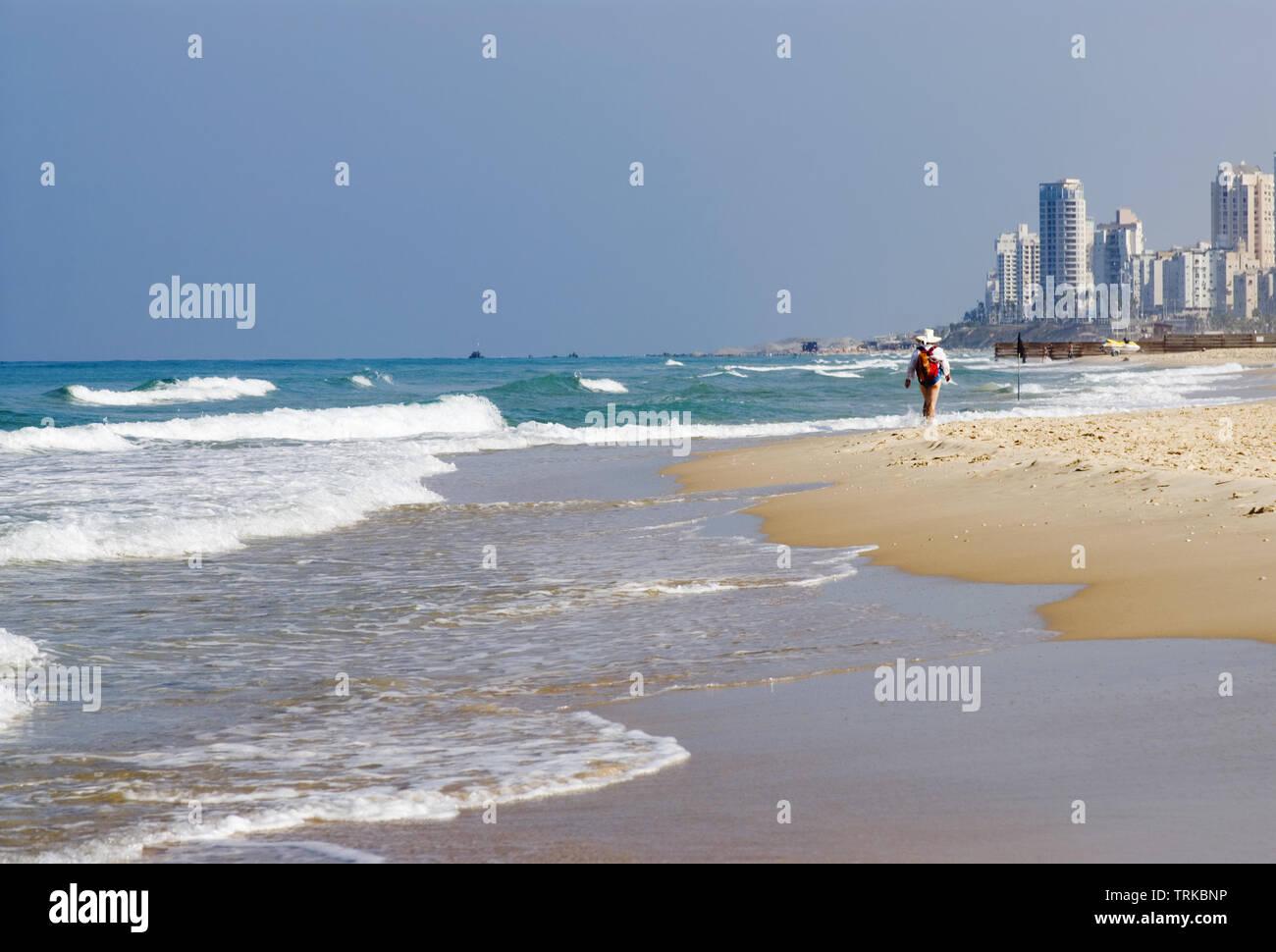 Beach in Tel Aviv, Israel. Surf wave, distant walking figure - Stock Image