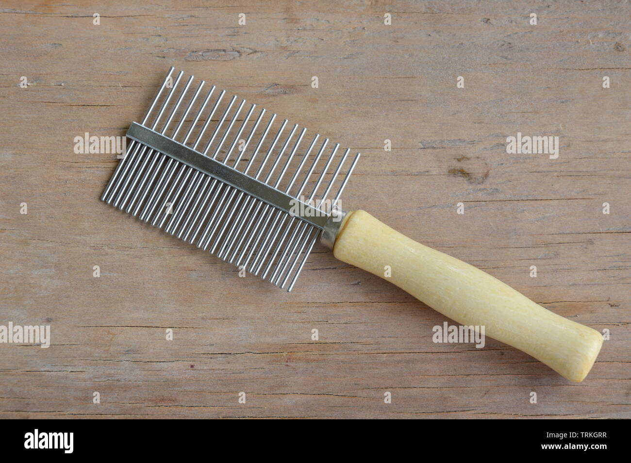 comb with teeth away and fine for dog and cat on wooden board - Stock Image