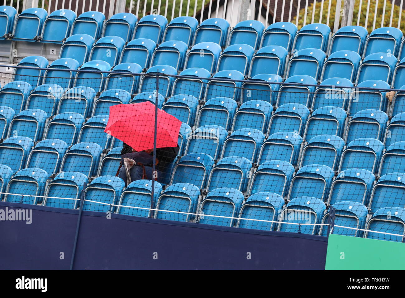 Surbiton, London: A single fan battles the rain in hope of seeing some tennis action later in the day at the 2019 Surbiton Trophy. Stock Photo