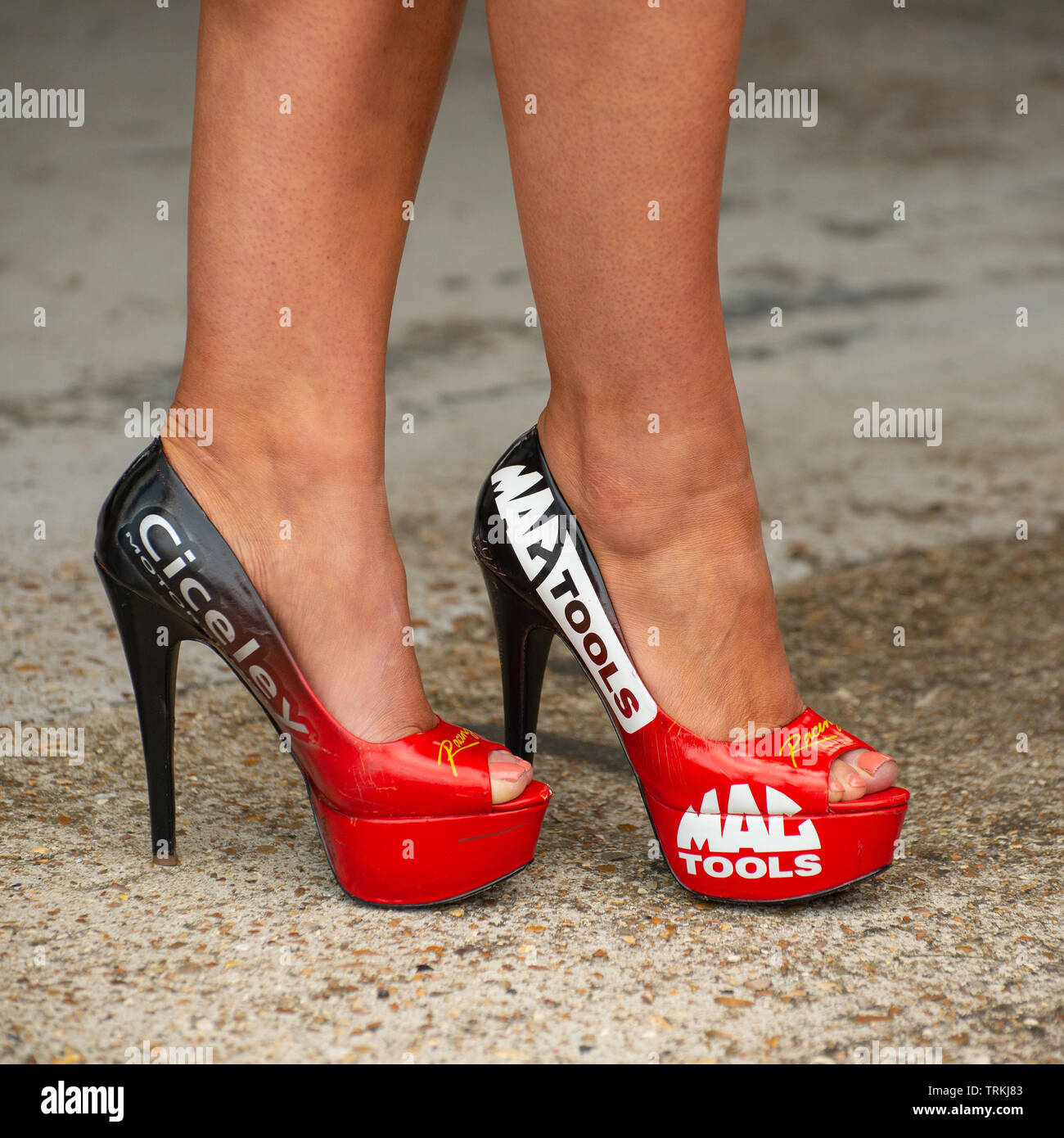 Ladies Legs in a Pair of Red and Black High Heel Shoes Advertising Mac Tools and Ciceley Motorsport - Stock Image