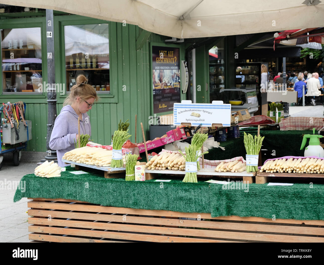 May 2019 - A young, blonde female sells white asparagus from a stand in the Victuals Market in Munich, Germany Stock Photo