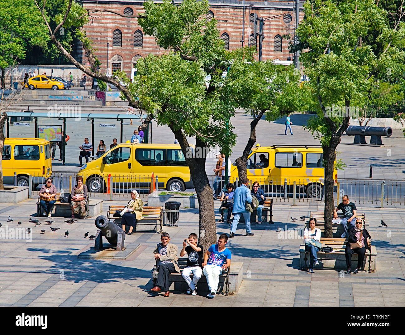 Istanbul, Turkey - 05/26/2010: People sitting on benches at bosporus strait coast, yellow taxis trees, canons replicas, sunny day. Stock Photo