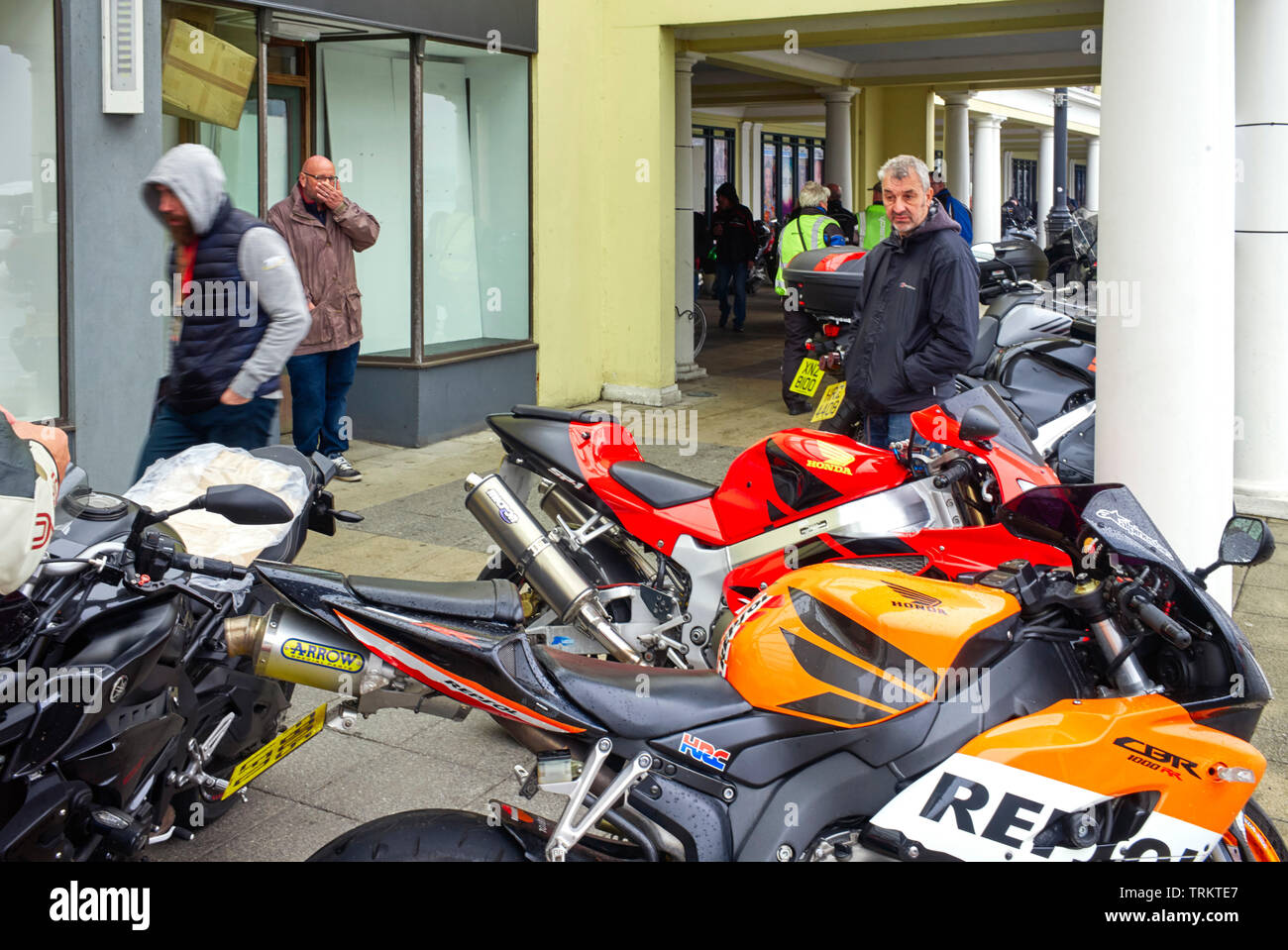 Visiting TT race fans looking at bikes during wet weather, including a man yawning - Stock Image