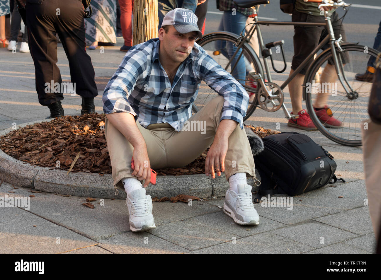Moscow, RUSSIA - June 7, 2019: Protest held in Moscow over arrest of investigative journalist Ivan Golunov. Man sitting on the lawn - Stock Image