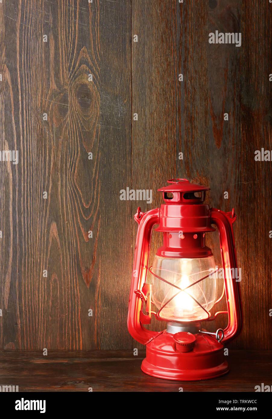 Lantern kerosene oil lamp, on wooden background - Stock Image