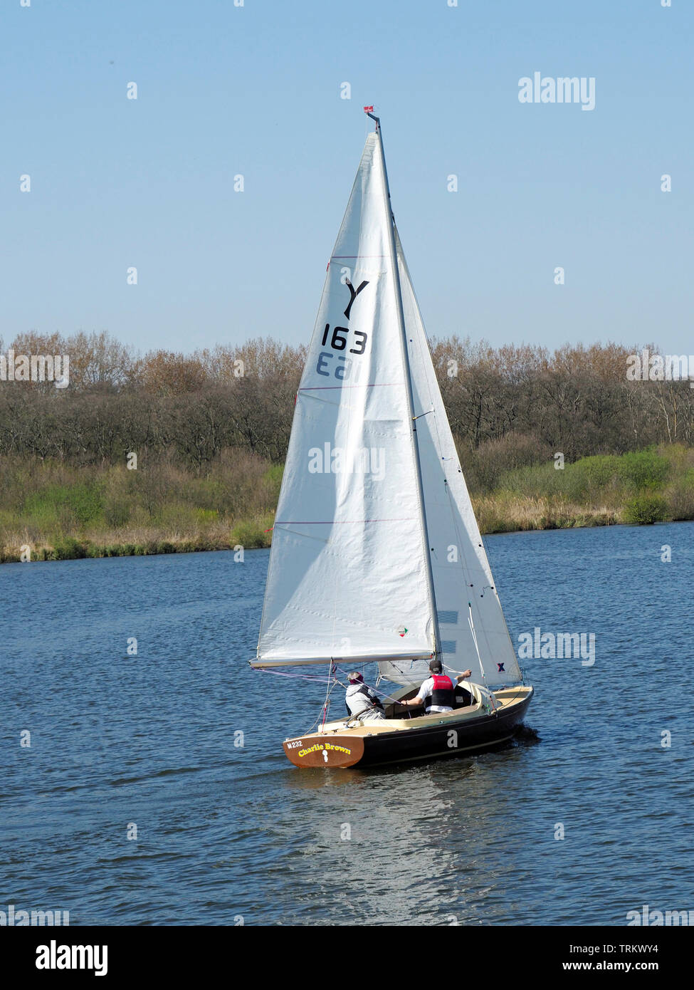 Sailing is a popular pastime on the Norfolk Broads. This small sailboat is making its way along the Rover Bure near Wroxham. Stock Photo