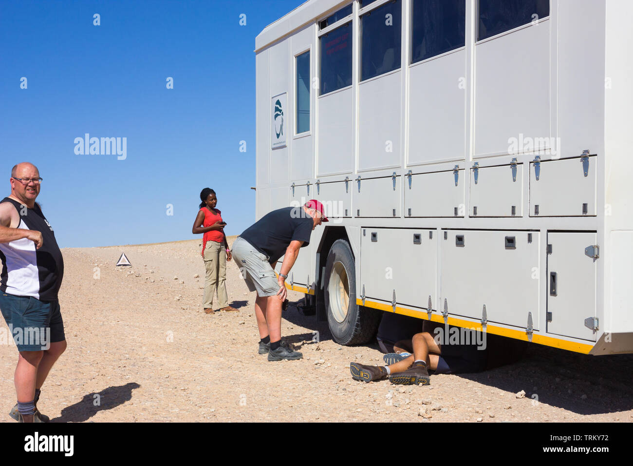 African overland tour truck or vehicle broken down and stuck on the side of a deserted desert dirt road in Namibia, Africa with people and tourists - Stock Image