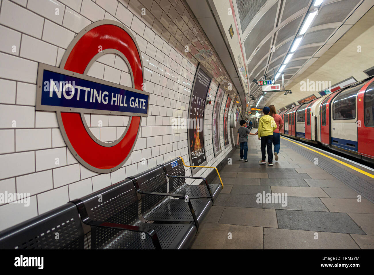 A mother and her son walk down the platform at Notting Hill Gate London Underground platform having arrived on a train. - Stock Image