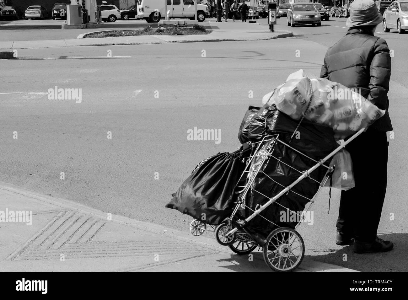 Old lady collecting used bottles to get some cash , Montreal, Canada - Stock Image