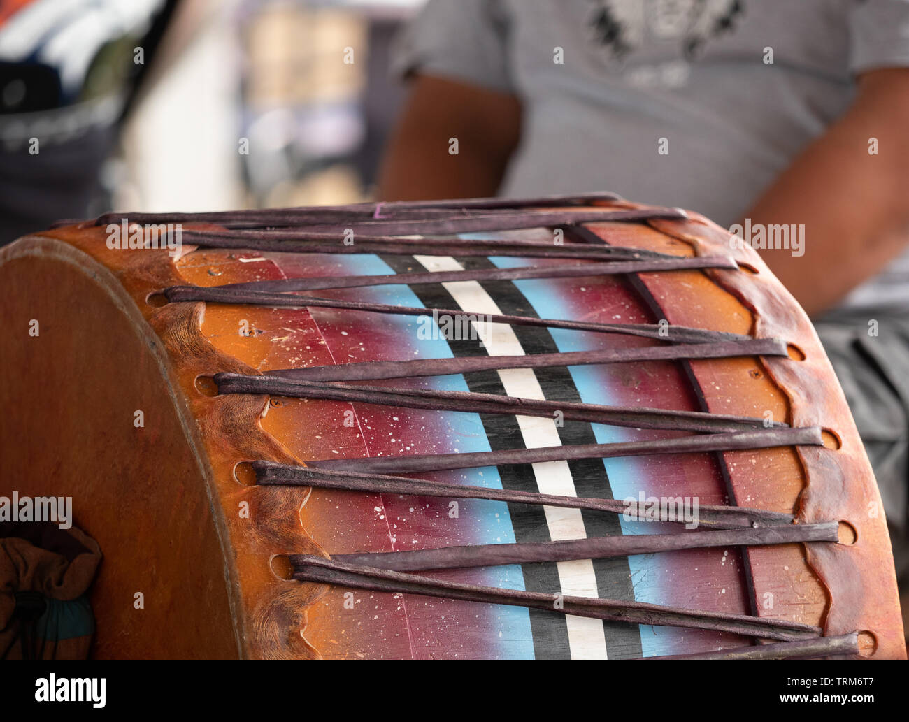 Close up of a wood and leather powwow drum with a drummer in the background. Shallow depth of field. - Stock Image