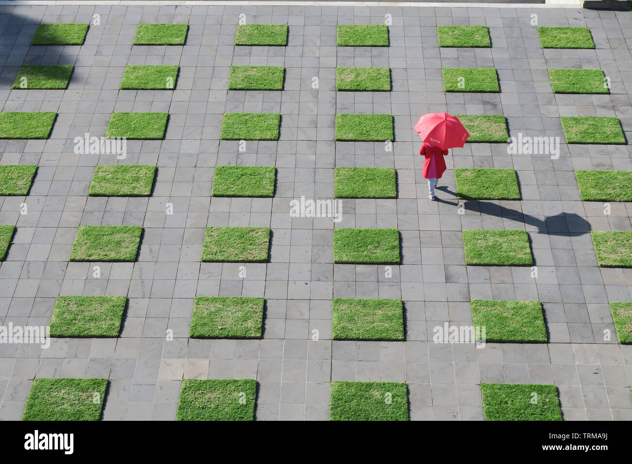 Melbourne Australia scenes: A solitary figure with a red umbrella walking around the Shrine of Remembrance Melbourne. - Stock Image