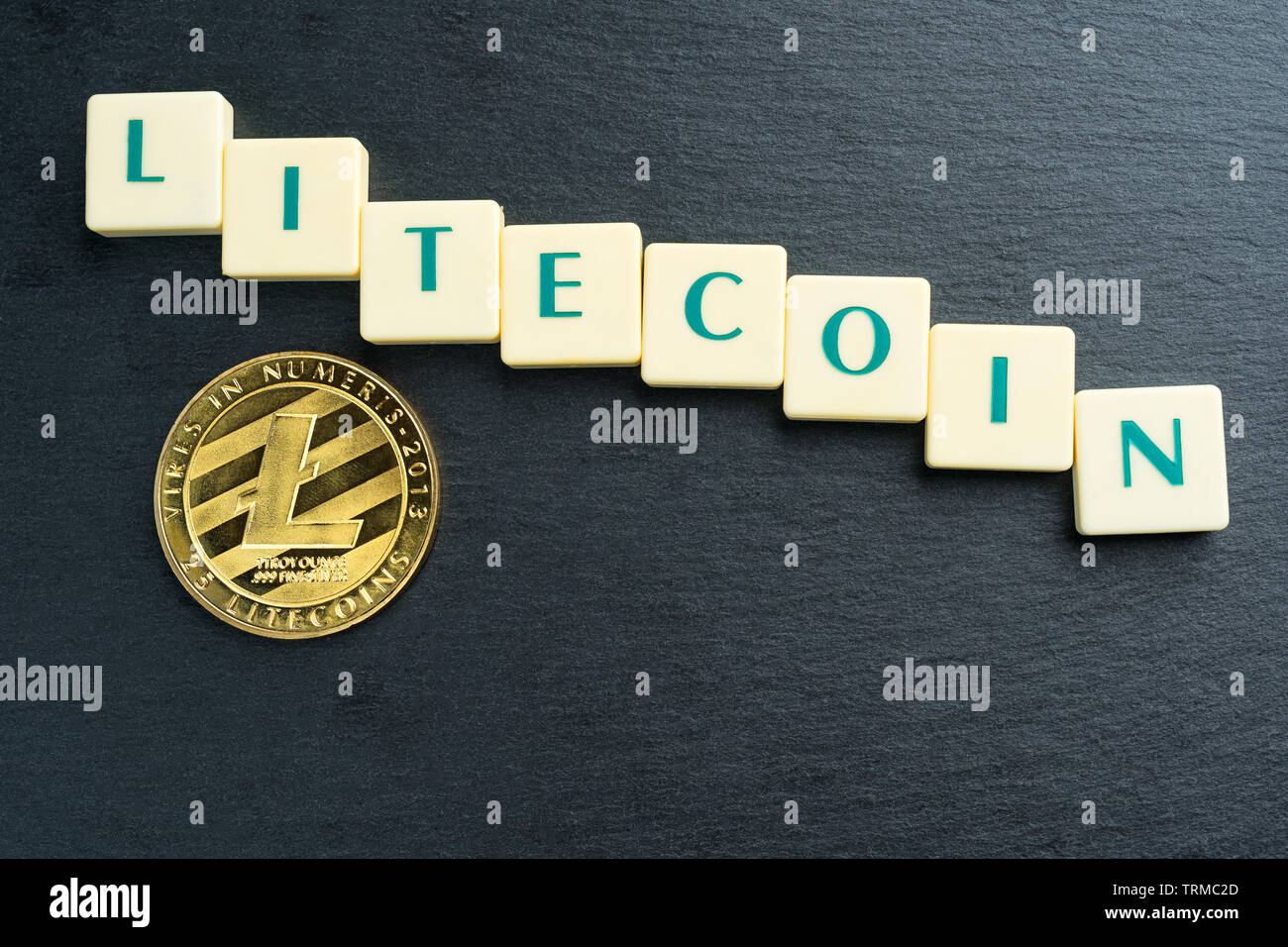 Physical Litecoin gold coin with text made out of letter tiles. Cryptocurrency decline or bear market. Copy space on the top bottom. - Stock Image