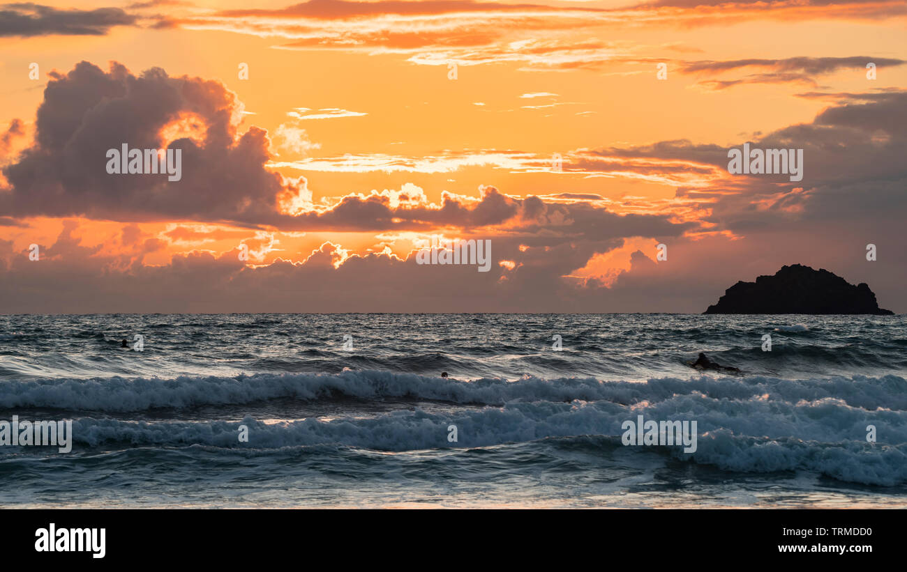 A dramatic sky at dusk with an orange afterglow and dark clouds above a choppy sea. Cornwall, UK. - Stock Image