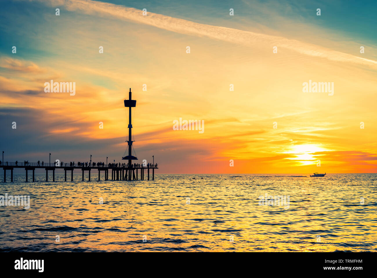People silhouettes on Brighton Jetty and modern boat at sunset, South Australia - Stock Image