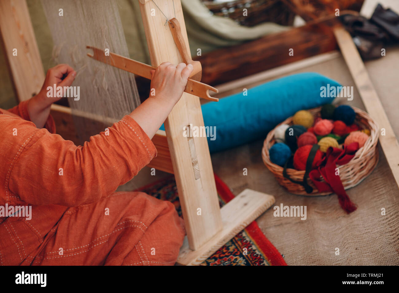 Woman makes thread, yarn and fabric - Stock Image