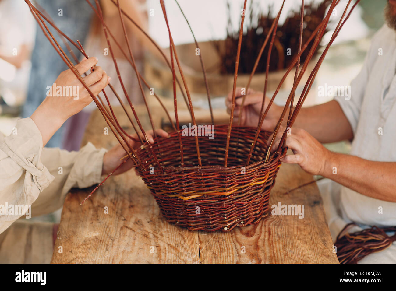 Master man weaves a basket of twigs - Stock Image