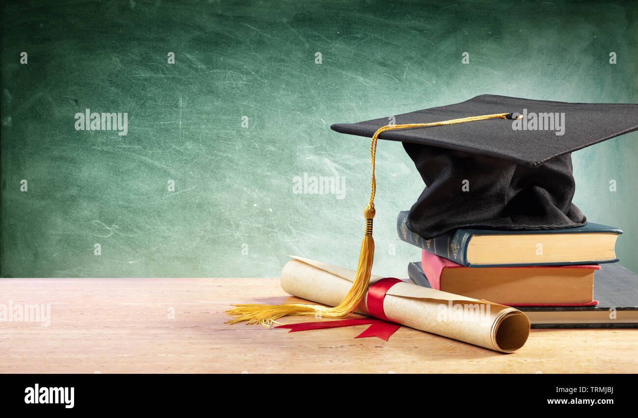 Graduation Cap And Diploma On Table With Books - Stock Image