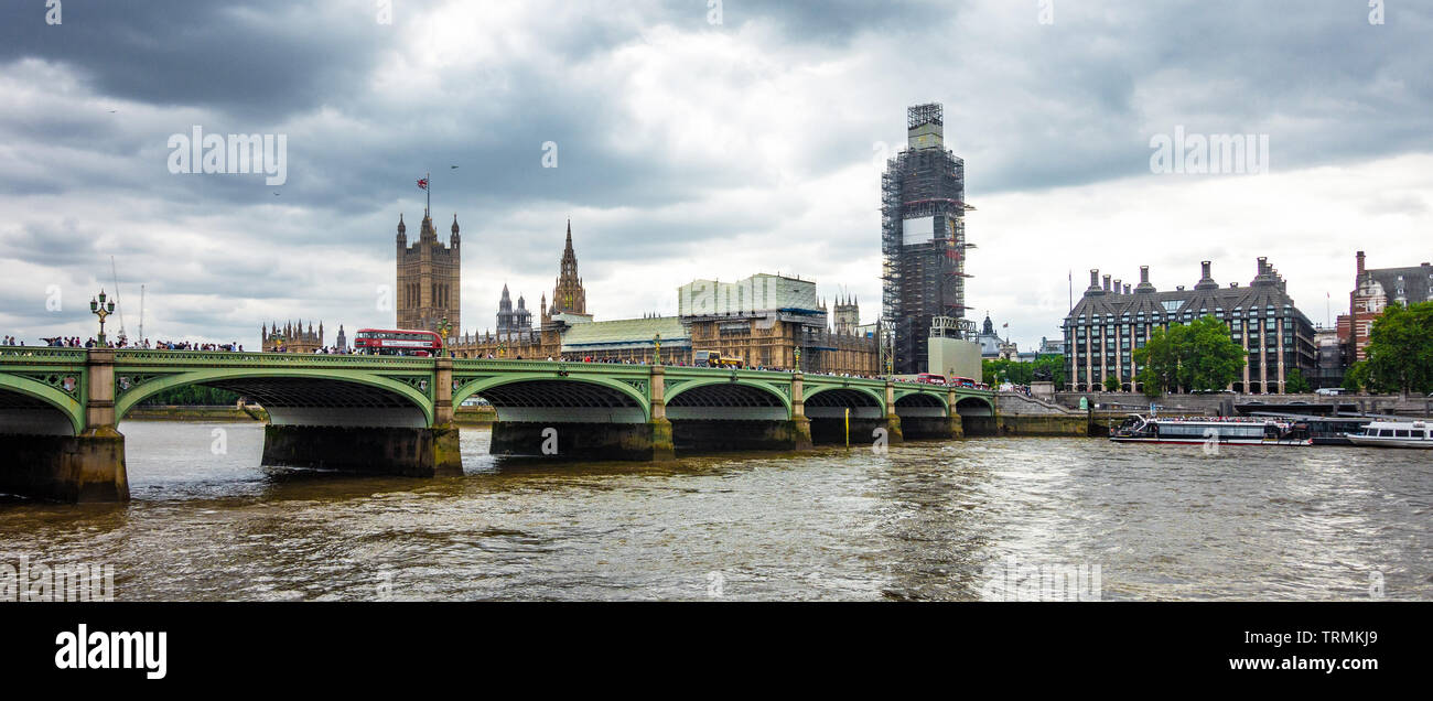 A view of Westminster Bridge spanning The RIver Thames with The Houses of Parliament beyond with The Elizabeth Tower covered by scaffolding for repair - Stock Image
