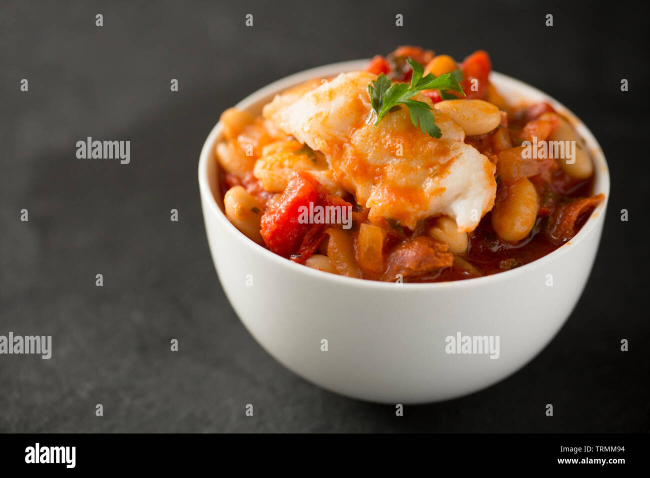 A pollack and chorizo sausage fish stew made with tomatoes, roasted red bell peppers, tinned tomatoes, chopped onions, cannellini beans and parsley. T - Stock Image