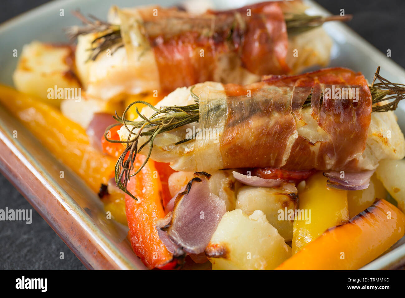 Fillets of line-caught pollack, Pollachius pollachius, that have been marinated in a garlic and lemon juice before being wrapped in Parma ham with fre - Stock Image
