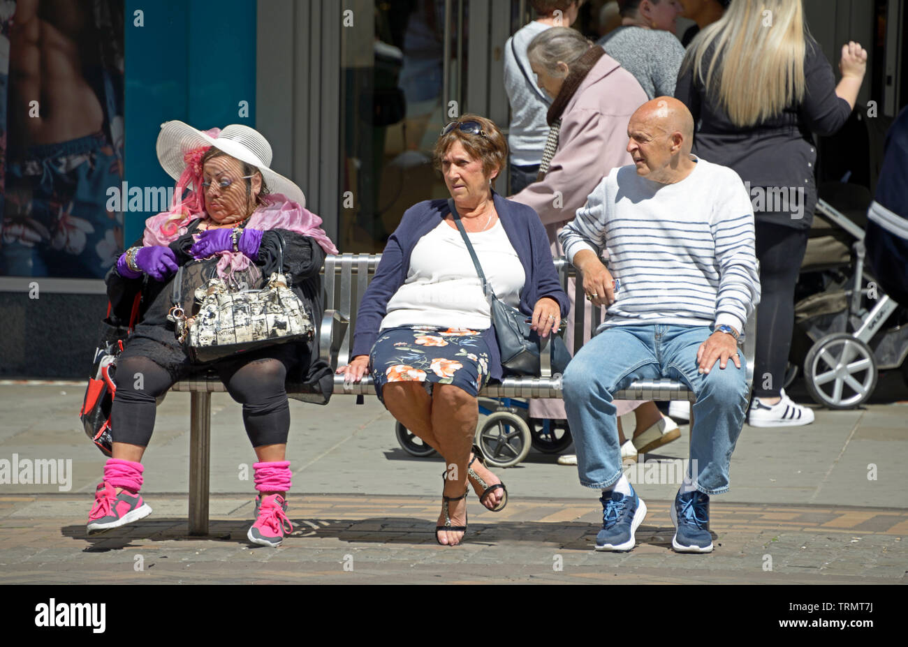 Bizarrely dressed lady sitting on bench with couple - Stock Image
