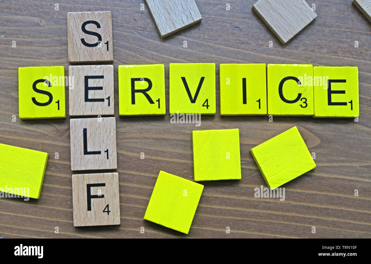 Self-Service spelt out in yellow and wooden Scrabble letters Stock Photo