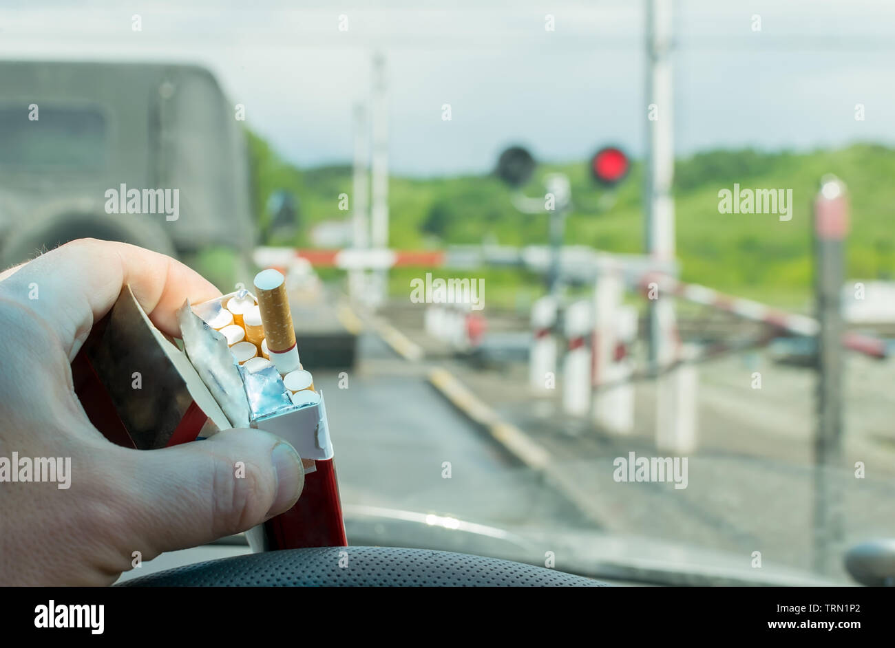 View of the driver hand with a pack of cigarettes on the steering wheel of the car, which stopped before a closed railway crossing at a red light Stock Photo