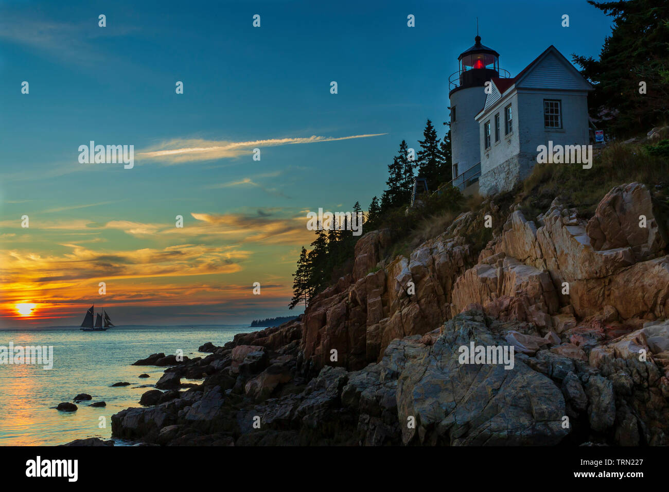 Bass Harbor Head Lighthouse and sail boat at sunset in Acadia National Park, Maine - Stock Image
