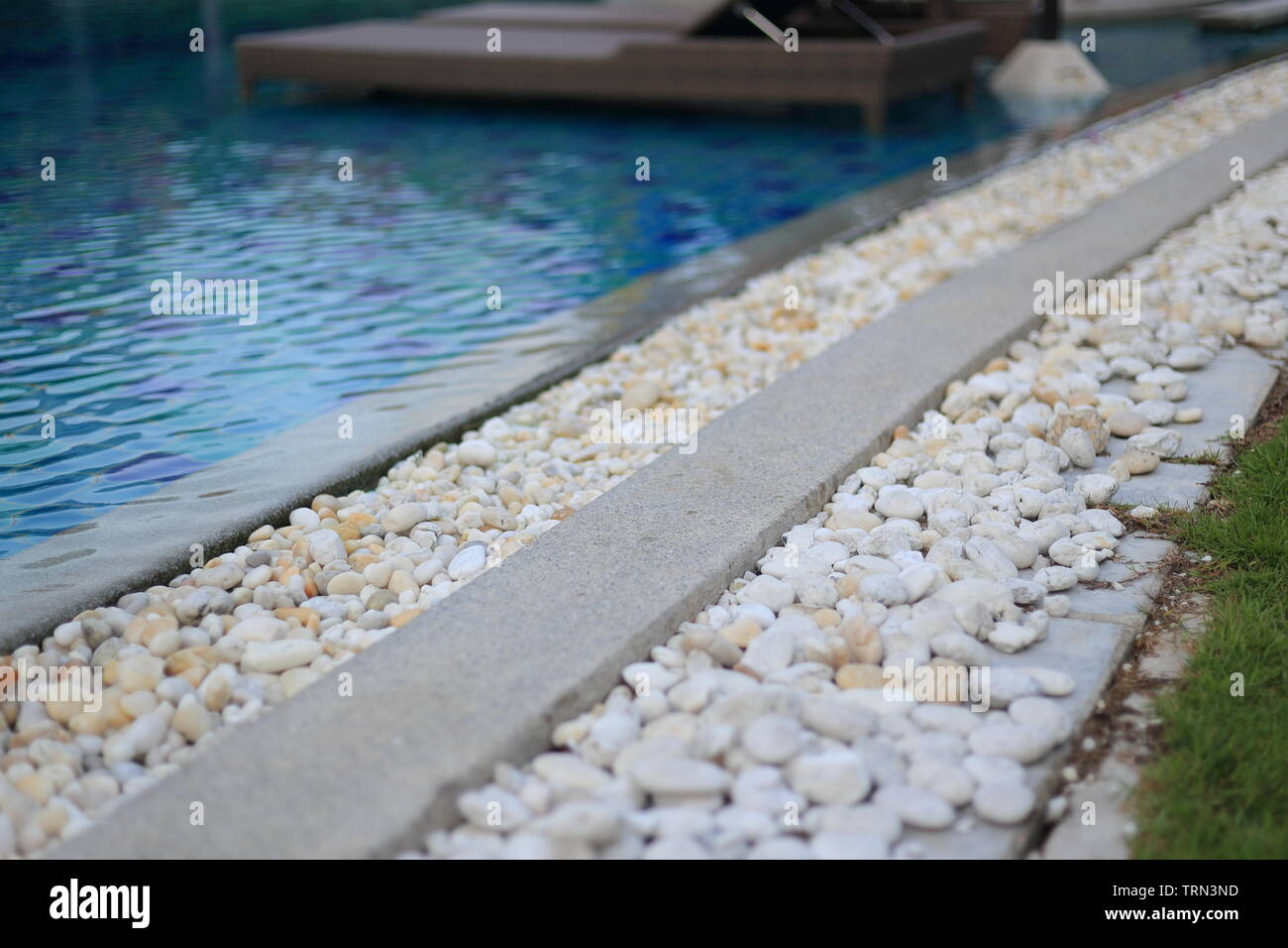 swimming pool drainage system grating covered with round white river stone pebble. swimming pool architectural detail design. White pebble contrasting - Stock Image