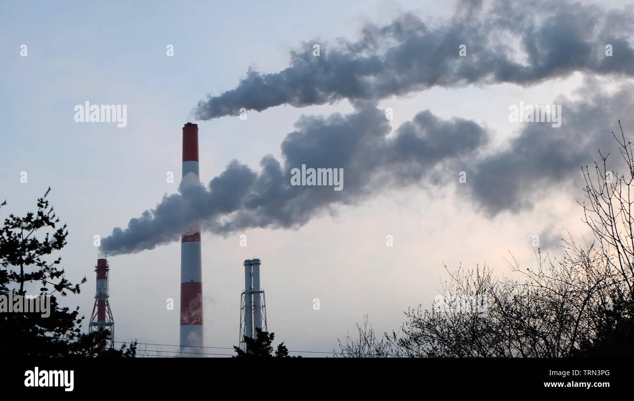 Thick smoke emission from tall industrial chimneys. - Stock Image